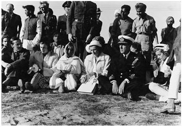 The Mountbattens sitting cross legged on the ground at Gandhiji's funeral.